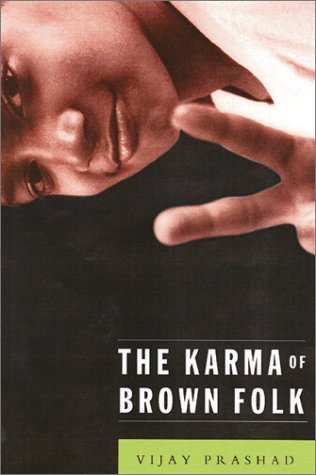 """The cover of The Karma of Brown Folk shows a photograph of a young brown boy giving a """"peace"""" sign. The photo is on it's side, giving the cover a feeling of being off-balance."""